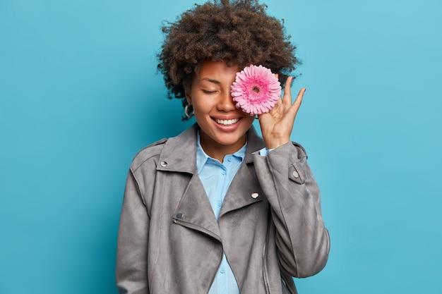 Binnen foto van professionele vrouwelijke bloemist dekt oog met gerbera daisy, maakt creatieve compositie van bloemen, bereidt boeket te koop, glimlacht in grote lijnen, staat