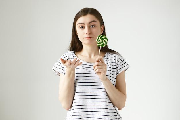 Binnen geïsoleerd schot van serieuze mooie terloops geklede jonge europese vrouw met lolly, gebaren, onzekerheid en twijfel uitend, onzeker over het eten van suiker, zoet, ongezond voedsel
