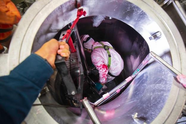 Binnen mannelijke twee werknemer in de inspectie glanzende tank roestvrij chemische blower frisse lucht in de beperkte ruimte.