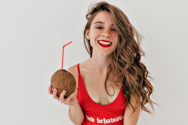 Binnen portret van heldere schattige mooie vrouw met lang lichtbruin haar met rode lippenstift draagt rode zwembroek met kokosnoot over grijze muur