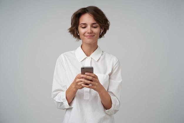 Binnen schot van aangenaam uitziende jonge vrouw met kort bruin haar, gekleed in een wit overhemd tijdens het poseren, smartphone in haar handen houden en bericht typen