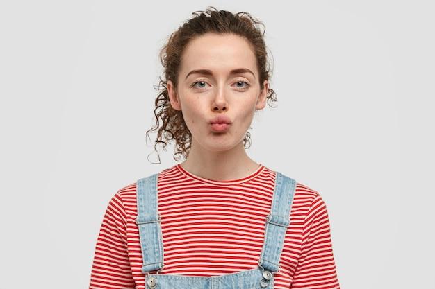 Binnen schot van aantrekkelijk krullend jong vrouwelijk model wil iemand op afstand kussen, lippen pruilen