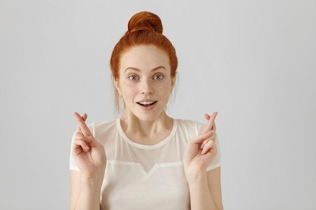 Binnen schot van aantrekkelijk roodharig meisje met haarbroodje met opgewonden, bijgelovige en naïeve blik