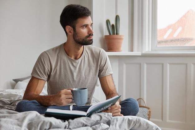 Binnen schot van aantrekkelijke bebaarde man die thuis poseren tijdens het werken