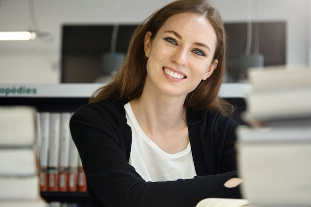Binnen schot van aantrekkelijke blanke tiener vrouw met lang donker haar zit aan bureau met veel leerboeken