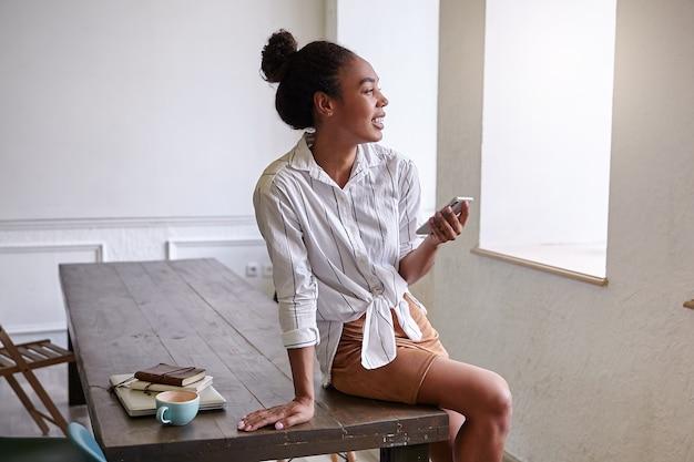 Binnen schot van aantrekkelijke donkere vrouw met broodje kapsel zittend op houten tafel, kijkt uit raam vreugdevol en smartphone in de hand te houden