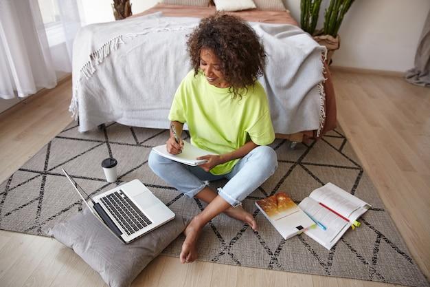 Binnen schot van aantrekkelijke donkere vrouw met bruin krullend haar poseren over interieur, haar huiswerk voorbereiden met laptop, boeken en notities