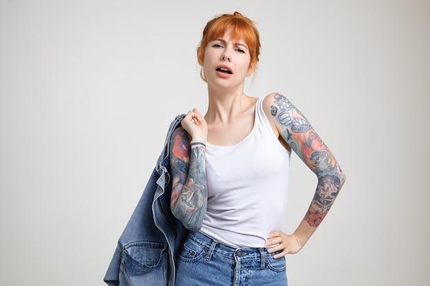 Binnen schot van aantrekkelijke eigenwijs jonge getatoeëerde vrouw met foxy haar, zelfverzekerd camera kijken terwijl staande tegen een witte achtergrond in vrijetijdskleding