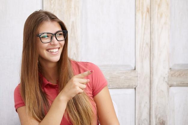 Binnen schot van aantrekkelijke jonge blanke vrouw die een stijlvolle bril draagt, vrolijk lacht, plezier heeft en haar wijsvinger zijwaarts richt