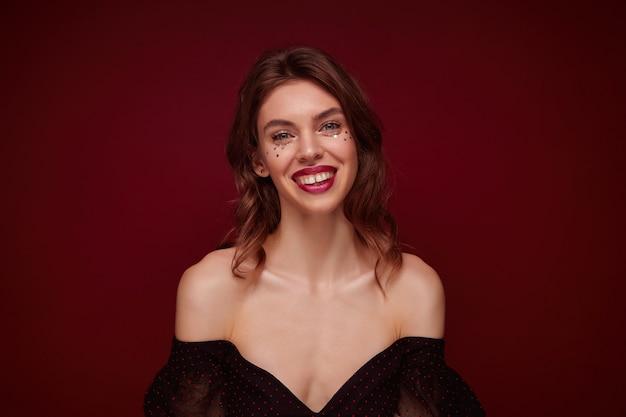 Binnen schot van aantrekkelijke jonge bruinharige vrouw met golvend kapsel die vrolijk kijkt en haar witte perfecte tanden demonstreert, geïsoleerd
