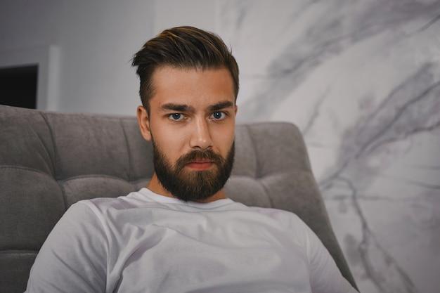 Binnen schot van aantrekkelijke jonge europese man met stijlvol kapsel en dikke baard camera staren met serieuze blik, zittend op de bank thuis. mensen, levensstijl en menselijke gezichtsuitdrukkingen