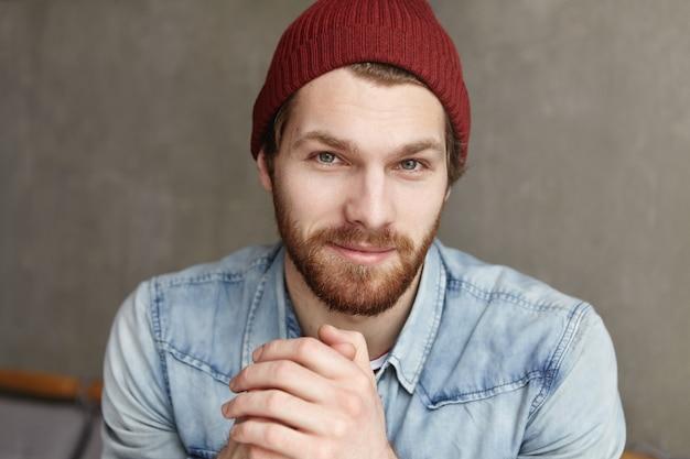 Binnen schot van aantrekkelijke jonge hipster student met baard ontspannen bij coffeeshop