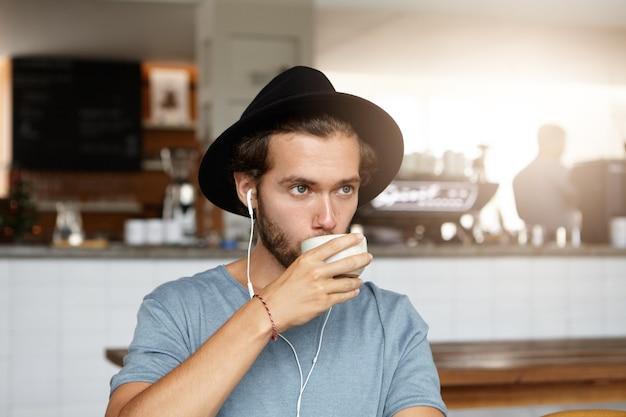 Binnen schot van aantrekkelijke jonge man in stijlvolle hoed koffie of thee drinken, ontspannen in café alleen, luisteren naar muziek online op oortelefoons