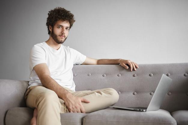 Binnen schot van aantrekkelijke jonge ongeschoren mannelijke ondernemer in vrijetijdskleding zittend op de bank met generieke laptop, op afstand werken, businessplan maken of e-mail verzenden