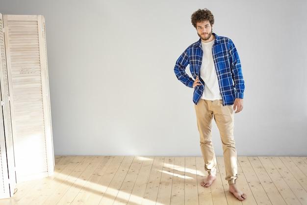 Binnen schot van aantrekkelijke modieuze jonge europese bebaarde mannelijk model dragen van trendy beige spijkerbroek en geruite blauw shirt poseren blootsvoets op houten vloer thuis, hand houden op zijn taille