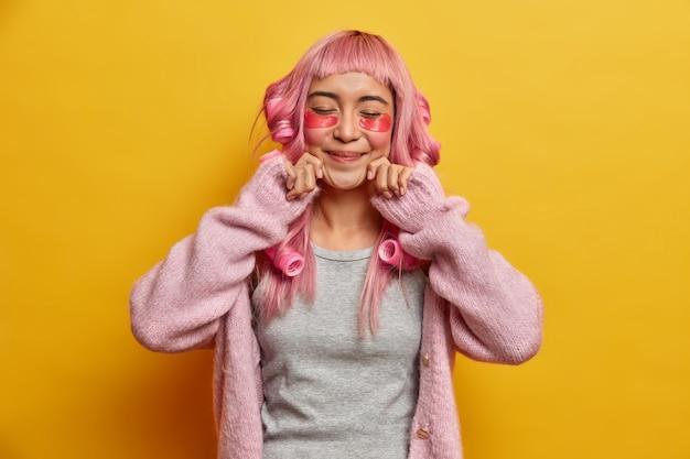 Binnen schot van aziatische vrouw houdt handen in de buurt van de mond, sluit de ogen met tevredenheid, draagt haarrollers om krullend kapsel te maken