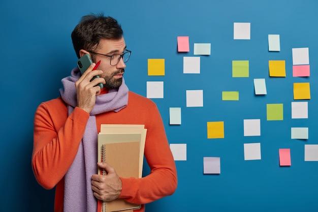 Binnen schot van bebaarde man heeft telefoongesprek, houdt pen en notitieboekjes vast, kijkt aandachtig naar plaknotities, studeert binnen, bereidt cursuspapier voor, studeert thuis.