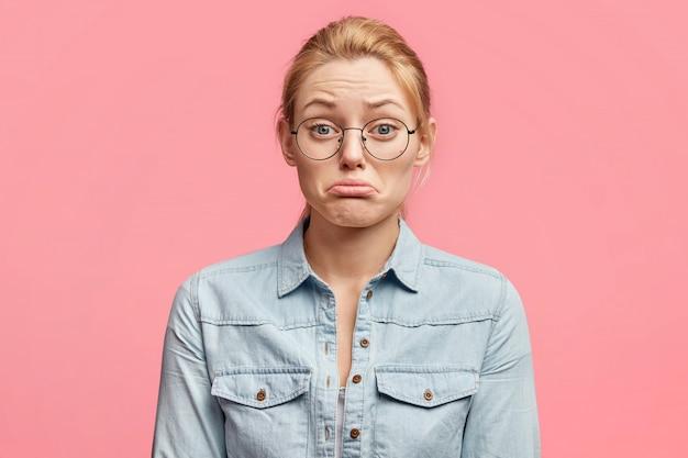 Binnen schot van bedroefd vrouw met boos expressie, heeft problemen met echtgenoot relatie, onderlip krommen in ontevredenheid, modieuze kleding draagt