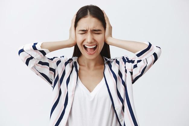 Binnen schot van beu boos europese vrouw in gestreepte blouse, schreeuwend van depressie, oren bedekkend met handpalmen met gesloten ogen, schreeuwend om verlichting van stress, intens staande over grijze muur