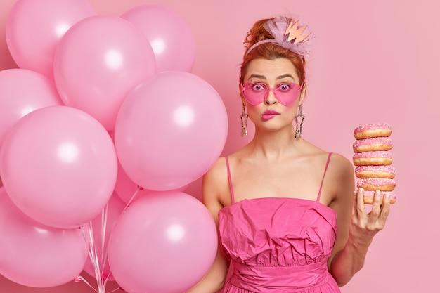 Binnen schot van bezorgde glamour vrouw bijt lippen en houdt een stapel donuts