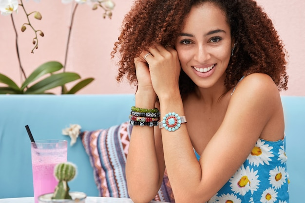 Binnen schot van blij jonge mooie vrouw heeft afro kapsel, gekleed in zomerkleding, vormt op blauwe sofa met cocktail in gezellig café met orchidee