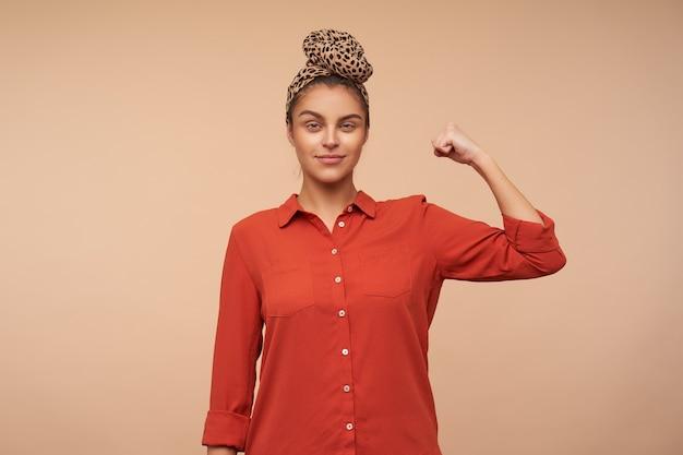 Binnen schot van blije jonge bruinharige vrouw gekleed in een rood shirt die haar hand opheft en aandachtig naar de voorkant kijkt met een lichte glimlach, geïsoleerd over beige muur