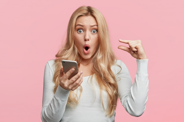 Binnen schot van blonde mooie vrouw met afgeluisterde blauwe ogen, nonchalant gekleed, houdt slimme telefoon vast, controleert online account, geïsoleerd over roze muur. geschokt vrouw met aantrekkelijk uiterlijk modellen in