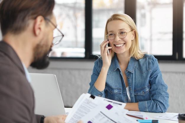 Binnen schot van blonde vrouw met zakelijk gesprek met collega