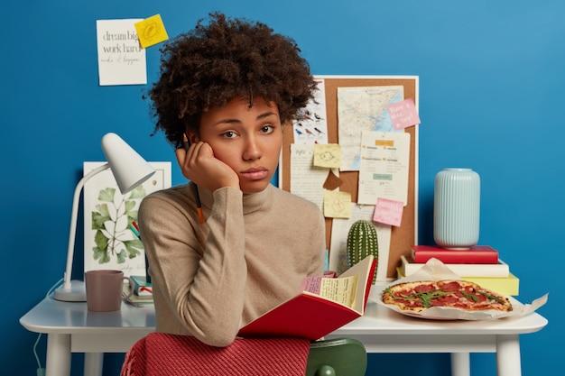 Binnen schot van boos afro meisje heeft droevige gezichtsuitdrukking, houdt geopende notitieblok, moe van examenvoorbereiding