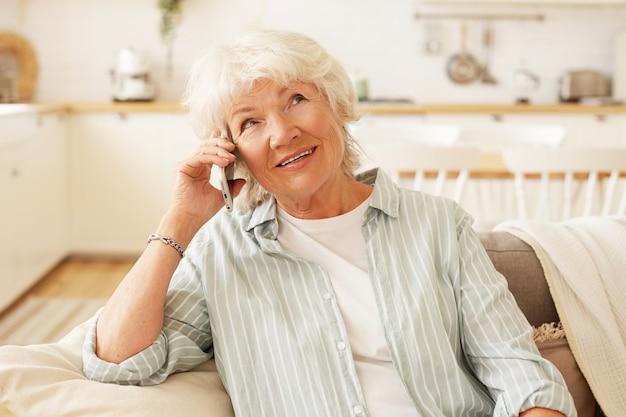 Binnen schot van charmante vriendelijke senior grijze haren vrouw met generieke slimme telefoon dicht bij haar oor, gehoorprobleem, praten met haar vriend, comfortabel zitten op de bank in de woonkamer