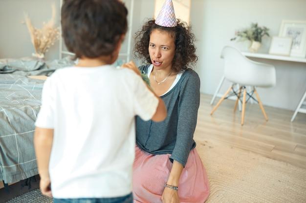Binnen schot van curly haired jonge spaanse vrouw met conische hoed op horen zittend op de vloer