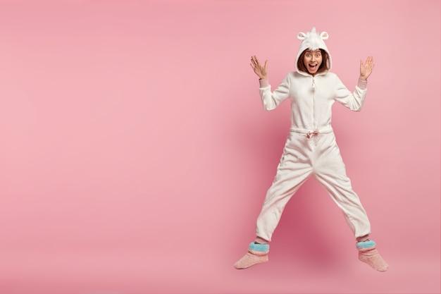 Binnen schot van dolblij gelukkig meisje in comfortabel huiselijk kigurumi kostuum, springt over roze ruimte