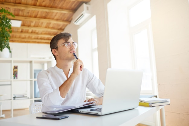 Binnen schot van doordachte geconcentreerde jonge zakenman draagt een wit overhemd op kantoor