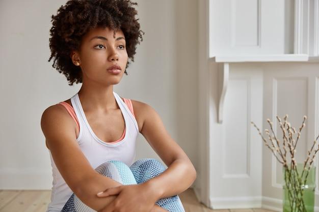 Binnen schot van doordachte jonge vrouw poseren in haar huis