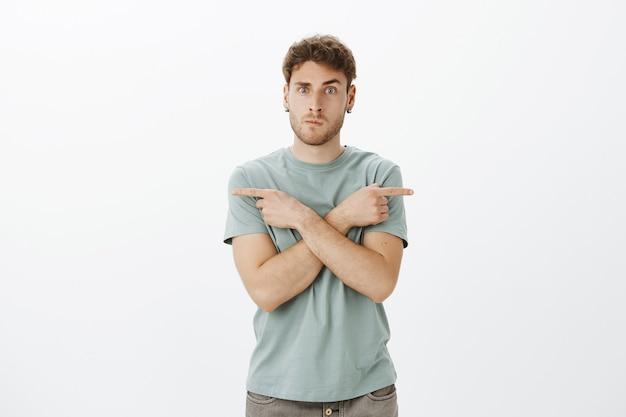Binnen schot van doordachte onrustige aantrekkelijk mannelijk model in oorbellen, lippen vouwen en handen over de borst kruisen terwijl ze in verschillende richtingen wijzen