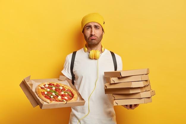 Binnen schot van droevige bezorger met pizzadozen
