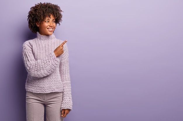 Binnen schot van een aangenaam uitziende zwarte vrouw met krullend haar, wijst naar de rechterbovenhoek, blij om iets te koop in de winkel te laten zien, gekleed in violette kleding op één toon. promotie