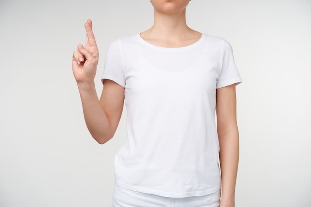 Binnen schot van een jonge vrouw die haar vingers kruist terwijl de letter r wordt weergegeven met behulp van het alfabet van de dood, wordt geïsoleerd op een witte achtergrond. menselijke handen en gebaren concept