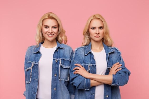 Binnen schot van ernstige blonde jongedame handen gevouwen houden terwijl staande op roze achtergrond met vrolijke blauwogige mooie blonde vrouw met golvend kapsel
