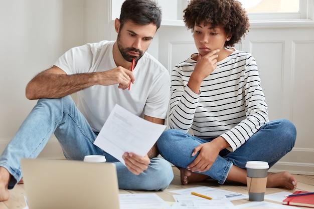 Binnen schot van ernstige gemengd ras vrouw en man studeren privé-regeling, werken vanuit huis