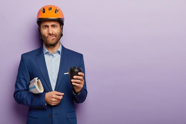 Binnen schot van ernstige zakenman poseren in stijlvol pak en rode helm op kantoor