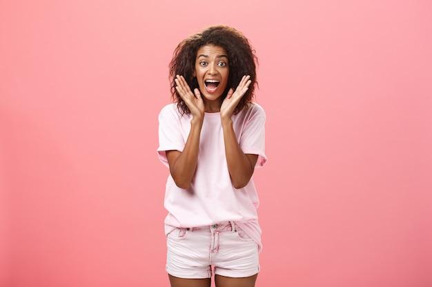 Binnen schot van expressieve opgewonden aantrekkelijke donkere huid volwassen vrouw in casual outfit schreeuwen van verbazing en vreugde met palmen in de buurt van gezicht reageren op geweldig nieuws met opwinding en geluk