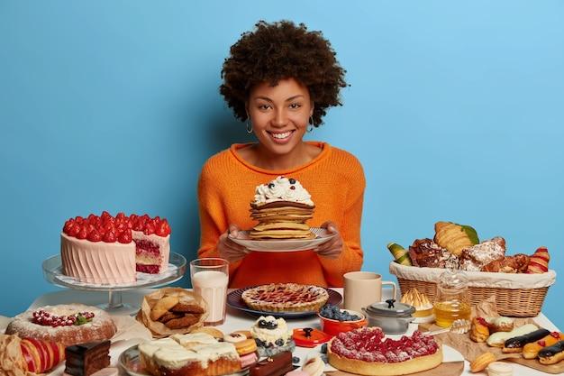 Binnen schot van gekrulde vrouw heeft zoete bakkerij lunchtijd, houdt plaat met heerlijke suikerachtige romige pannenkoeken, omgeven door gebakken zoetwaren