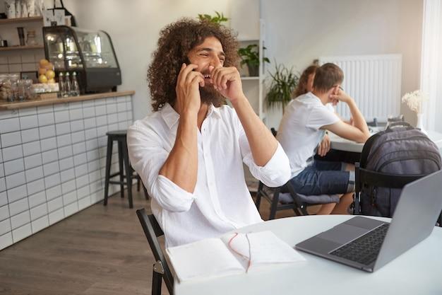 Binnen schot van gelukkig aangenaam uitziende jonge gekrulde man met een leuk gesprek aan de telefoon tijdens de lunch, lachen en zijn mond bedekken met de hand, het dragen van een wit overhemd