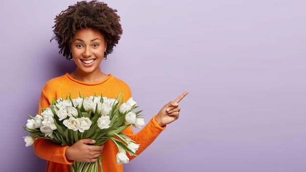 Binnen schot van gelukkig jong vrouwelijk model met afro-kapsel, wijst weg met wijsvinger