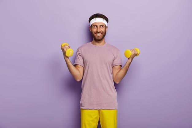 Binnen schot van gelukkig man met borstelharen, heft twee armen met gewichten, gekleed in casual outfit, treinen op biceps