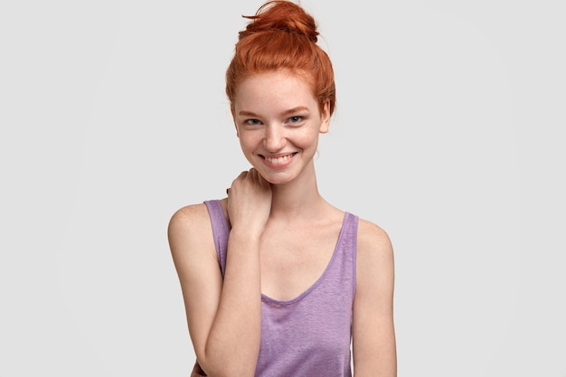 Binnen schot van gelukkig vrouwelijk model met gember haarbroodje, staat in casual paars vest, houdt de hand op de nek, toont natuurlijke schoonheid, geïsoleerd over witte muur, glimlacht van genot, maakt goede deal