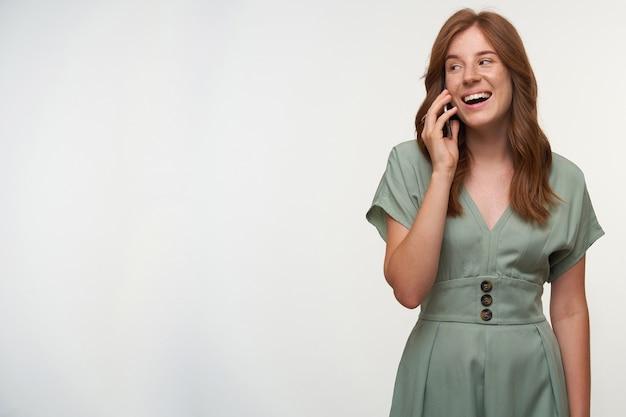 Binnen schot van gelukkige jonge roodharige vrouw in pastel jurk poseren, opzij kijken en breed glimlachen, aangenaam praten over de telefoon