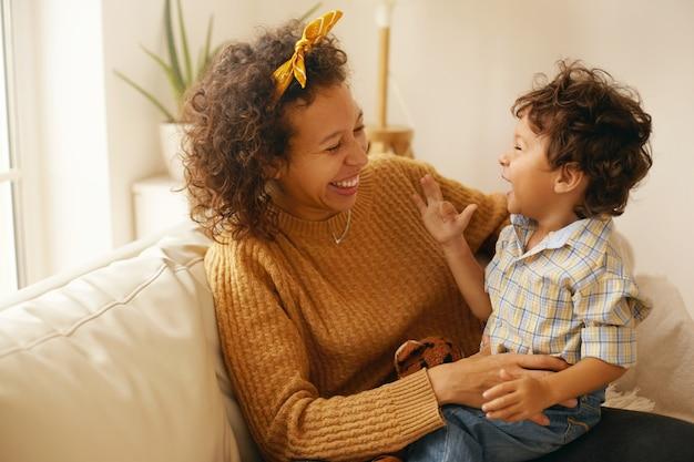 Binnen schot van gelukkige jonge spaanse vrouw met bruin golvend haar ontspannen thuis omhelst haar schattige peuter zoon. vrolijke moeder binding met zoontje, zittend op de bank in de woonkamer, lachen