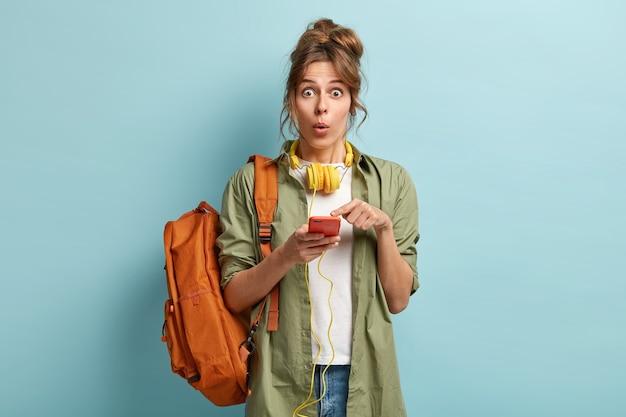 Binnen schot van geschokt hipster meisje wijst naar het scherm, ontvangt verbaasd bericht, luistert audiotrack met koptelefoon, draagt stijlvolle kleding